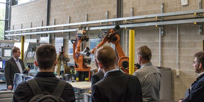 Zwei Roboterarme, die gemeinsam ein Werkstück bearbeiten, werden vor Zuschauern bei der Auftaktveranstaltung präsentiert.