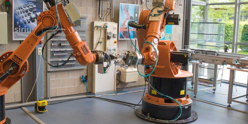 Bild von zwei Roboterarmen, die, bei der Auftaktveranstaltung, Bier in ein Weizenglas füllen.