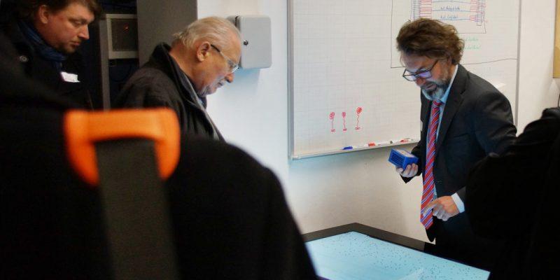Professor Meiller befindet sich vor einer Smart Table und präsentiert einem älteren Herren Inhalte