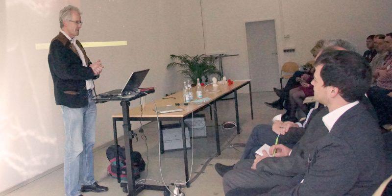 Professor Blöchl steht neben seinem Rechner und spricht zu den Teilnehmern der Veranstaltung