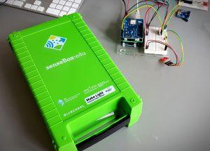 Das Bild zeigt das grüne Gehäuse der senseBox. Daneben sind einige Microcontroller zu sehen, die mit Kabeln verbunden sind.